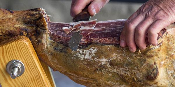Fotografía de la mano de un hombre cortando un jamón serrano