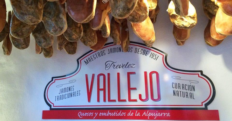 Cartel con el logotipo de Jamones Vallejo con varios jamones sobre él, una empresa con jamones denominación de origen a diferencia de los productos de indicación geográfica