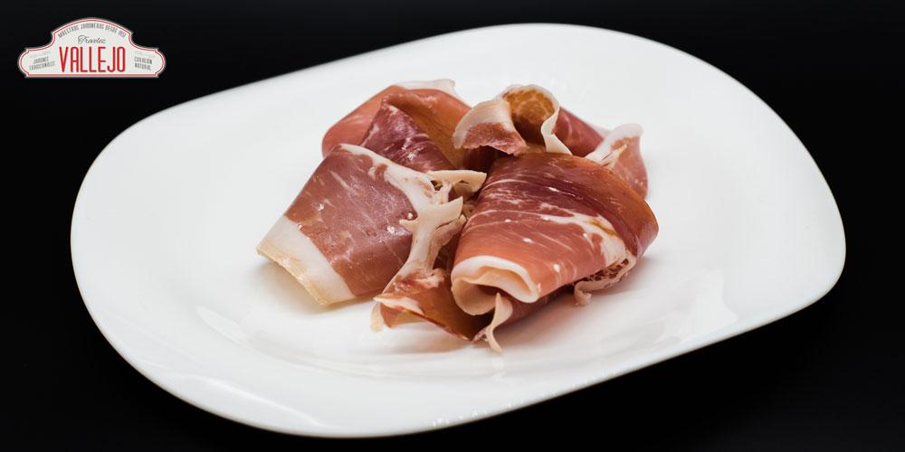 Jamón serrano Vallejo sobre un plato. Cortar jamón bien es importante para realzar su sabor