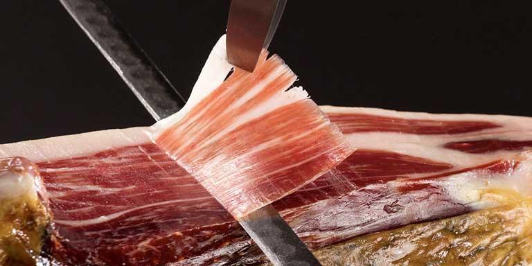 En la foto se observa una cortador de jamón realizando un corte de jamón profesional para conmemorar el aniversario de la escuela donde se imparte un exclusivo curso de cortaros de jamón